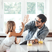 Father giving his daughter a high five in their kitchen